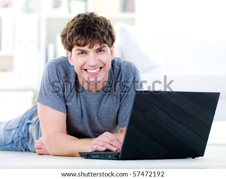 Portrait of happy young  man with laptop - indoors