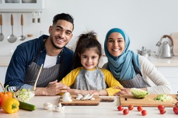 Portrait Of Happy Young Middle Eastern Family Cooking Together In Kitchen, Cheerful Arabic Parents And Their Little Daughter In Aprons Sitting At Table While Preparing Tasty Food Together