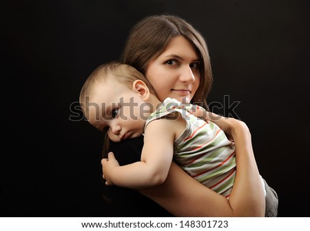 portrait of happy young mother and toddler on black background - stock photo
