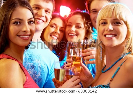 Portrait of happy young people holding glasses of champagne