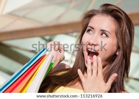 Portrait of happy young shopper surprised sales - stock photo