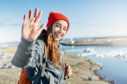 portrait of happy young smiling woman in warm clothing and knitted red hat with orange backpack in Ice Lagoon in Iceland with background of sea. a woman is waving a hand with a happy look and a smile