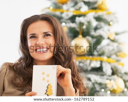 Portrait of happy young woman and christmas postcard near christmas tree