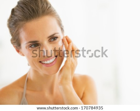 Portrait of happy young woman applying cream in bathroom
