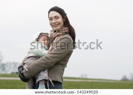 Portrait of happy young woman carrying sleeping baby in park
