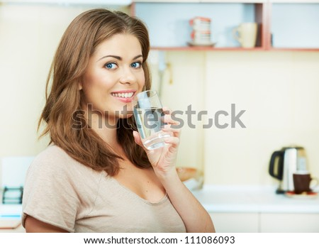 Portrait of happy  young woman drinking water against kitchen background.