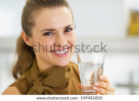 Portrait of happy young woman drinking water in kitchen