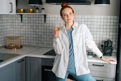 Portrait of happy young woman drinking white wine standing in light kitchen room. Dreamy lady tasting champagne alone while preparing food. Concept of leisure activity red-haired female at home