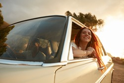 Portrait of happy young woman going on a road trip leaning out of window. Female enjoying travelling in a car with her boyfriend.