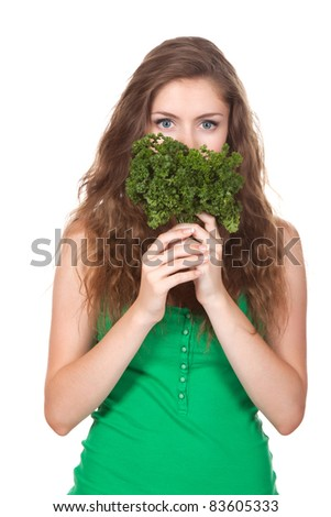 portrait of happy young woman hold green fresh leaf of raw fennel coriander parsley in hand close half face, with long brown curly hair - isolated on white background, concept of heath food, diet,