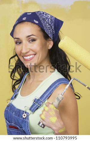 Portrait of happy young woman holding paint roller with