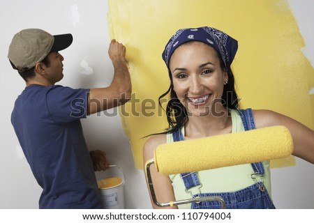 Portrait of happy young woman holding paint roller with man painting wall in background