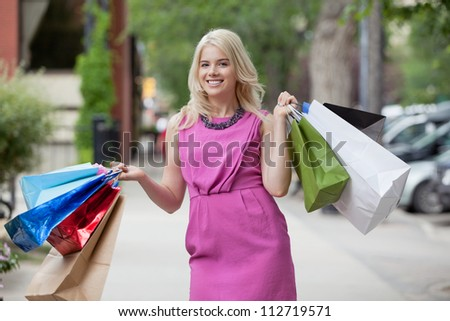 Portrait of happy young woman in pink dress carrying shopping bags on sidewalk