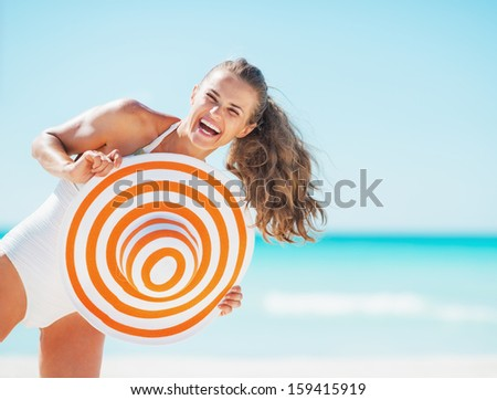Portrait of happy young woman in swimsuit with beach hat having fun time on beach