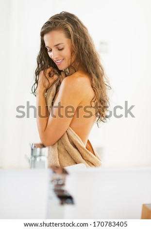 Portrait of happy young woman in towel in bathroom