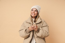 Portrait of happy young woman in winter coat laughing and using cellphone isolated over beige background