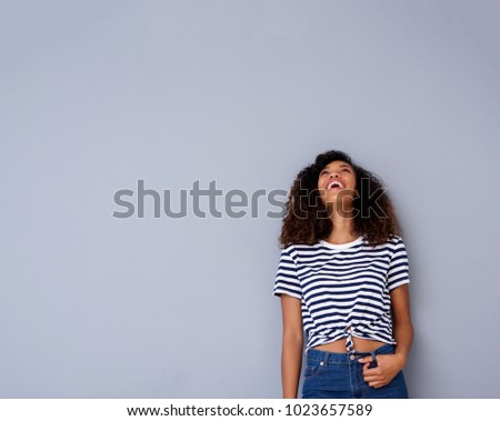 Portrait of happy young woman laughing and looking up