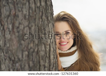 Portrait of happy young woman leaning against tree in winter park