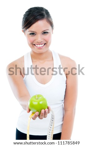 Portrait of happy young woman presenting apple and measuring tape over white background