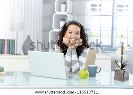 Portrait of happy young woman sitting in bright study, laptop computer, mug, green apple on desk.