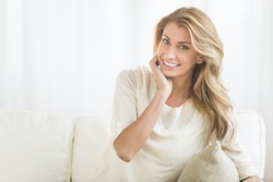 Portrait of happy young woman sitting on sofa at home