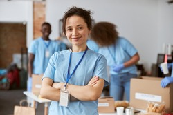 Portrait of happy young woman, volunteer in blue uniform smiling at camera while standing with arms crossed indoors. Team sorting, packing items in the background