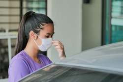Portrait of happy young woman wearing face medical mask standing in carpark. She want to go out and protection by mask from covid-19 / covid19 / corona virus. Epidemic spread protection safety concept