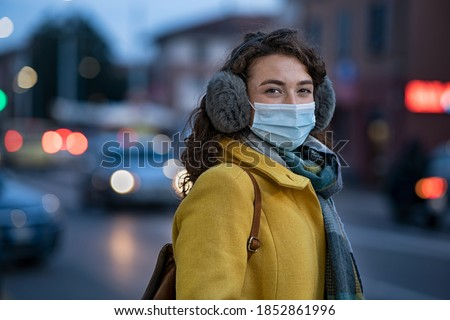 Portrait of happy young woman wearing medical protective mask outdoors and looking at camera. Smiling girl wearing surgical mask for virus protection standing outdoor in winter evening.