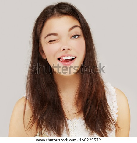 Portrait of happy young woman winking and laughing - stock photo