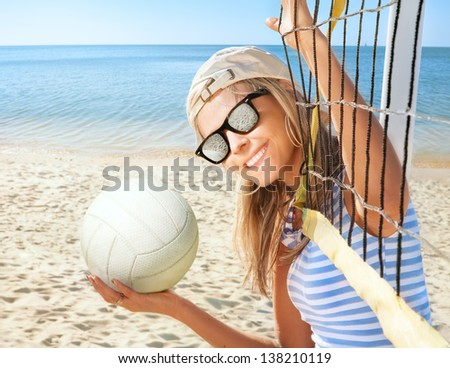 Portrait of happy young woman with ball on sea beach