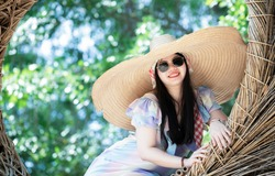 Portrait of happy young woman with dark long hair in big wide brim straw hat and sunglasses wearing pastel dress - sitting on circle rattan chair at the botanical garden.