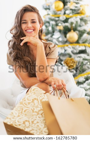 Portrait of happy young woman with shopping bags sitting near christmas tree