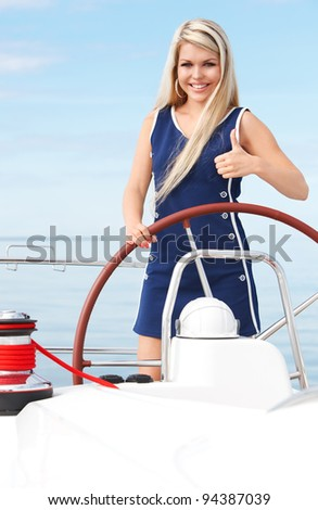 portrait of happy young woman with steering wheel showing thumb up on the yacht