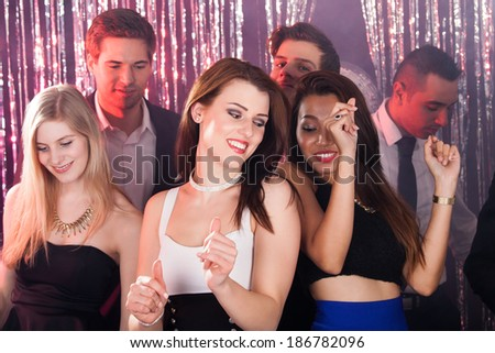 Portrait of happy young women dancing with friends at nightclub #186782096