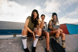 Portrait of happy young women sitting on ramp at skate park and smiling. Group of female friends at skate park.
