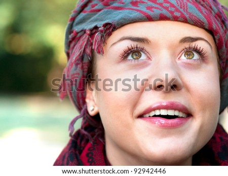 Portrait of healthy,cheerful  young woman wearing colorful scarf looking above  the camera