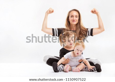 Portrait of healthy family of mother rising hands and playing children isolated at white background. #1150907522