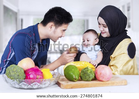 Portrait of healthy family with fresh fruits in the kitchen, man give fruit to his son