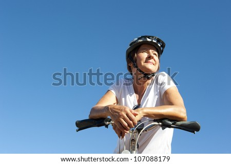 Portrait of healthy fit and sporty, confident and successful mature woman cycling on mountain bike, isolated with blue sky as background and copy space.