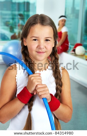 Portrait of healthy girl with blue hoop in gym