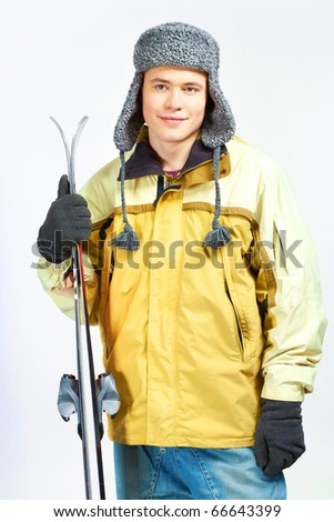 Portrait of healthy man with pair of skis looking aside and smiling