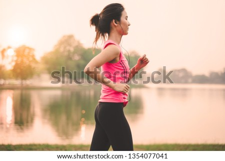 Portrait of healthy woman runner legs running exercise jogging on road, Woman fitness jog workout in the park during sunset #1354077041