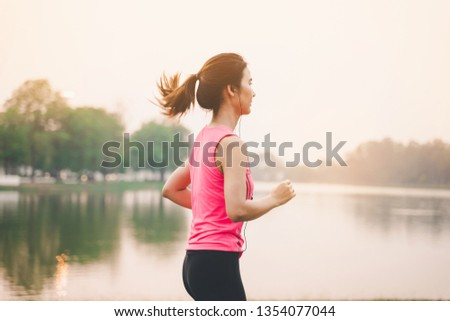 Portrait of healthy woman runner legs running exercise jogging on road, Woman fitness jog workout in the park during sunset #1354077044