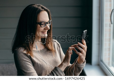 Portrait of healthy young brunette woman making facetime video calling with smartphone at home, using zoom meeting online app, social distancing, work from home, work remotely concept