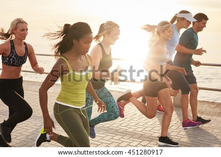 Portrait of healthy young men and women running race on seaside promenade. Group of young people sprinting outdoors at sunset.