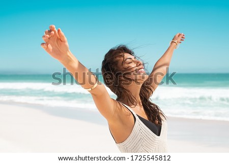 Portrait of healthy young woman standing on the beach with outstretched arms and feeling the breeze. Happy young woman feeling fresh and relaxing at ocean. Latin tanned woman with closed eyes. Photo stock ©