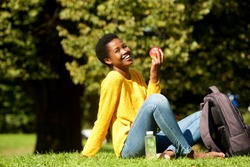 Portrait of healthy young woman with apple in park