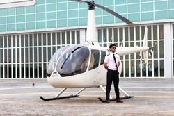 Portrait of helicopter pilot in uniform walk and standing outside with private helicopter background