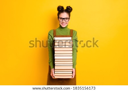 Portrait of her she attractive brainy diligent cheerful girl nerd carrying, many book 1 September new year semester grade isolated bright vivid shine vibrant yellow color background