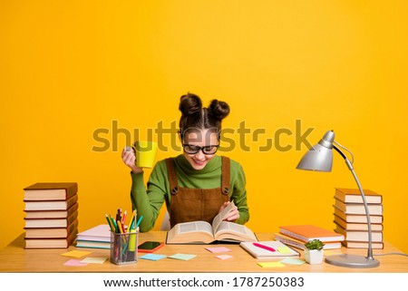 Portrait of her she attractive cheerful focused brainy woman nerd reading book learning grammar drinking beverage staying home isolated bright vivid shine vibrant yellow color background Stock photo ©
